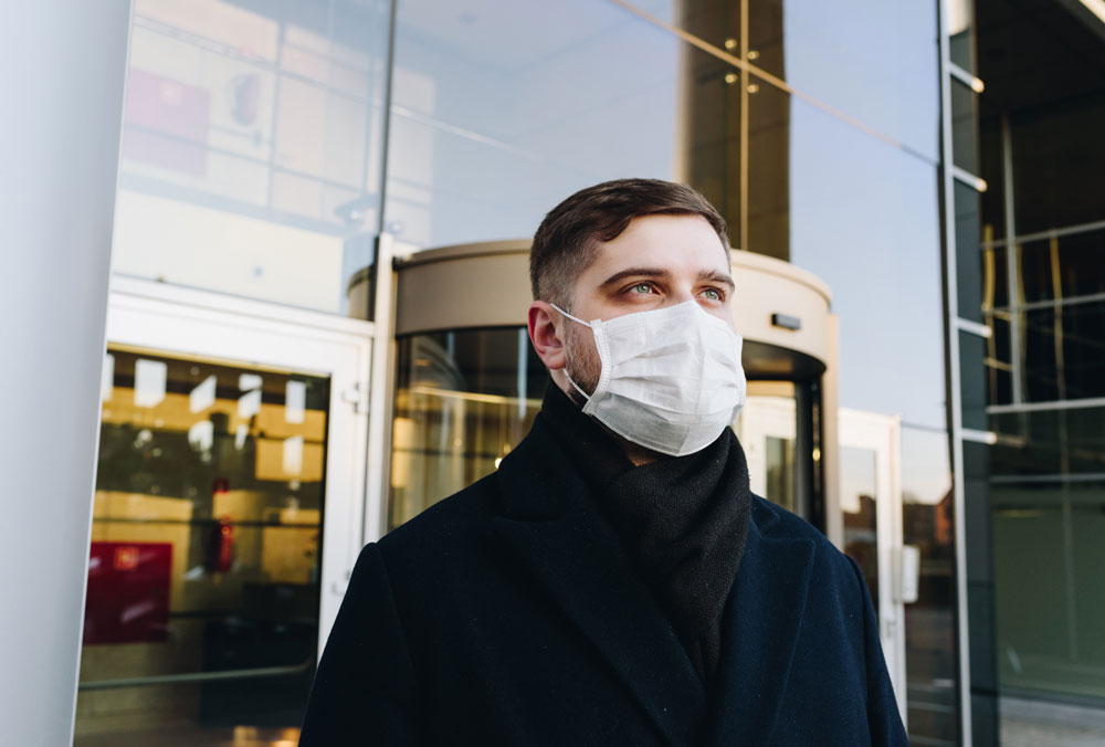 guy with mask near office building